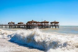 Beach palm huts on wooden dock in a wavy sea. End of summer season concept.