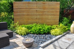 Beach pebbles, square cut flagstone and brick landscape pavers and simple plantings provide ample texture and contrast in this small contemporary backyard Asian inspired urban garden.
