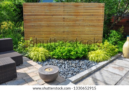 Beach pebbles, square cut flagstone and brick landscape pavers and simple plantings provide ample texture and contrast in this small contemporary Asian inspired urban garden.