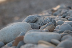Beach pebbles textured backdrop. Warm stone colours fading into the distance in soft sunset colours. A peaceful elegance. Beauty in simplicity. Abstract calming neutrality and ultimately grounding.