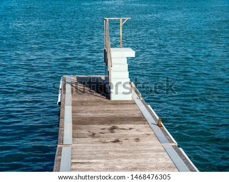 Beach pier with elevated platform for water jumping, sightseeing, fishing and snorkeling - calm sea in the perspective concept of solitude calmness and zen