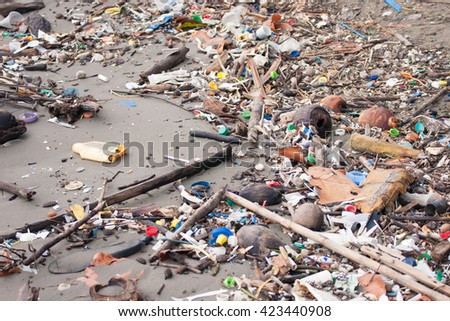 Beach pollution. Plastic bottles and other trash on sea beach of Livingston, Guatemala. (selective center focus)  stock photo