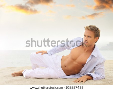 Beach portrait of a good looking young blond man in white pants and light blue shirt laying down looking off - stock photo