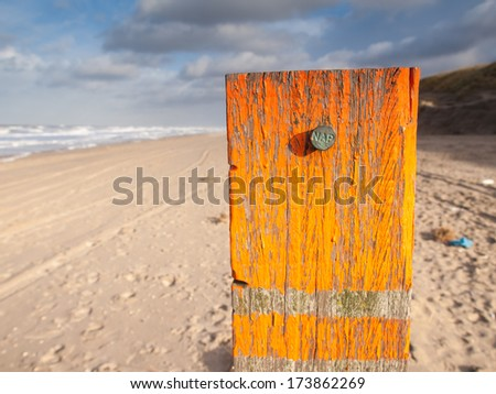 beach post with orange flaking paint carrying a metal marker nail indicating the dutch standard sea level datum point the Amsterdam Ordnance Datum (Normaal Amsterdamse Peil or NAP). Stok fotoğraf ©
