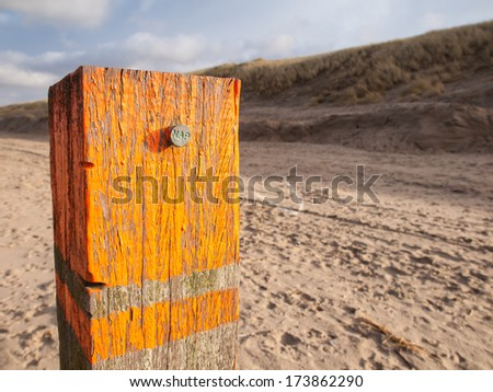 beach post with orange flaking paint carrying a metal marker nail indicating the dutch standard sea level datum point the Amsterdam Ordnance Datum (Normaal Amsterdamse Peil or NAP) with dunes behind Stok fotoğraf ©