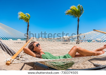 Beach relaxation sun tanning girl lying down on hammock relaxing sunbathing in Caribbean vacation holiday at resort hotel. Happy woman in sunglasses and cover-up dress laid back enjoying suntan.