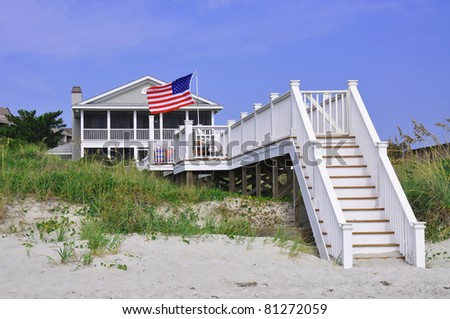 Beach rental on a summer day, with American Flag blowing in the wind - stock photo