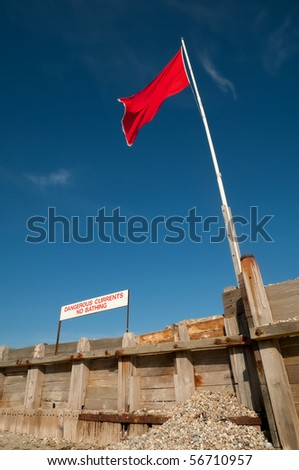 beach safety warning sign and flag against a clear blue sky