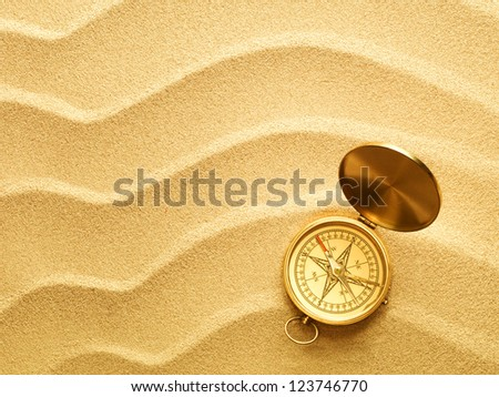 beach sand background and antique bronze compass