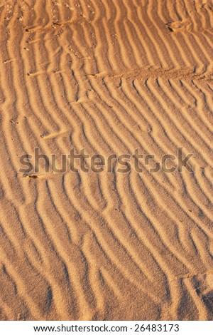 Beach sand background illuminated by sun - stock photo