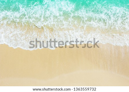Beach sand sea shore with blue wave and white foamy background,top view