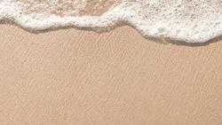 Beach sand sea water summer background. Sand beach desert texture. White foam wave sandy seashore top view.