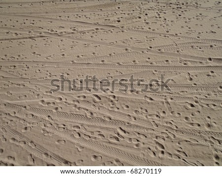 Beach Sand with foot prints and tire tracks on Santa Monica Beach. texture works well as abstract background. Sand pattern.