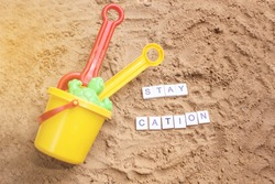 Beach sand with toys for the baby, water, the word holi stay in colored letters. Staycation content