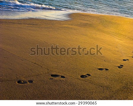 Beach Sand with Wet Footprints on Ocean Shore at Dusk