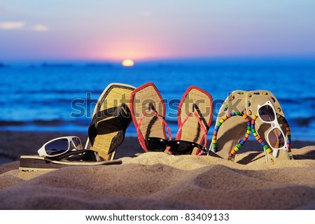 Beach sandals and glasses on the beach in evening