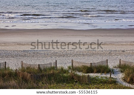 Beach scene of sand,surf,dune,sea grass,fence as early morning welcomes a beautiful day at the beach.