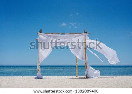 Beach shade with white gracefully fluttering fabric curtains on seashore. Sea breeze and white sand Photo stock ©