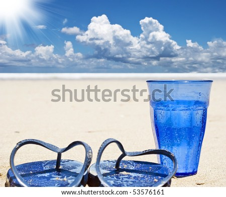 Beach shoes and a blue glass of sparkling water on a tropical island beach