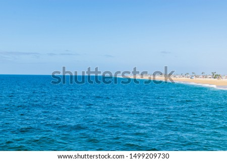 Beach shoreline in Southern California with waves reaching the shore on clear day and room for copy space #1499209730