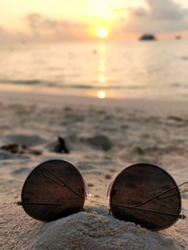 beach side picture of sun glasses in sun set