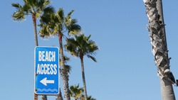 Beach sign and palms in sunny California, USA. Palm trees and seaside signpost. Oceanside pacific tourist resort aesthetic. Symbol of travel holidays and summertime vacations. Beachfront promenade.