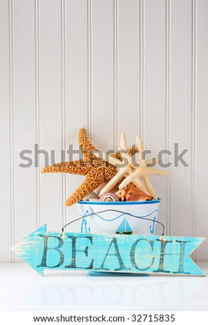 Beach sign with starfish in a sand bucket