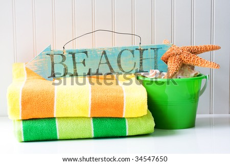 Beach sign with towels and sand bucket