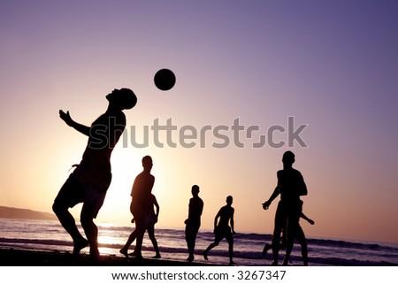 Un juego del balompié en la playa en la puesta del sol