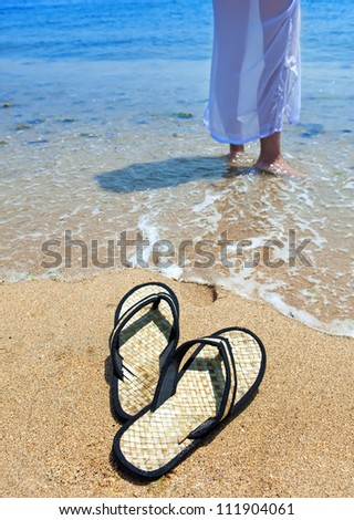 Beach slippers on sand, and female feet at a sea edge