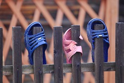 Beach sneaker on the fence.Flip flops on the fence. Shoes hanging on a wooden fence. People dry beach shoes. Old boots that fall into the ocean. Slippers are dried in the fresh air.