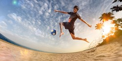 Beach soccer player in action. Sunny beach wide angle