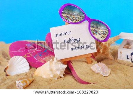 beach still life with greetings text written on easel ,flip-flop,seashells and seaside reflected in  sunglasses