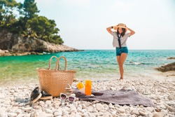 beach stuff straw hat and bag with flippers and sun protection cream at seashore woman on background