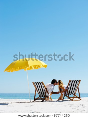 Beach summer couple kissing on island vacation holiday in the sun on their deck chairs under a yellow umbrella. Idyllic travel background. #97744250