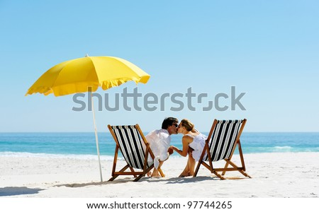 Beach summer couple kissing on island vacation holiday in the sun on their deck chairs under a yellow umbrella. Idyllic travel background. #97744265