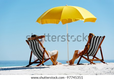 Beach summer couple on island vacation holiday relax in the sun on their deck chairs under a yellow umbrella. Idyllic travel background. #97745351