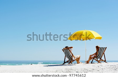 Beach summer couple on island vacation holiday relax in the sun on their deck chairs under a yellow umbrella. Idyllic travel background. #97745612