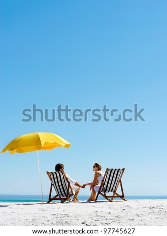 Beach summer couple on island vacation holiday relax in the sun on their deck chairs under a yellow umbrella. Idyllic travel background. #97745627