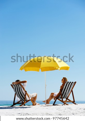 Beach summer couple on island vacation holiday relax in the sun on their deck chairs under a yellow umbrella. Idyllic travel background. #97745642