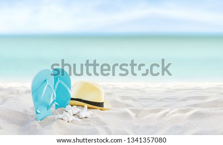 Beach summer holiday banner background. Flip flops and hat on sand near ocean. Summertime accessories on seaside. Tropical vacation and relax travel concept. Top view and copy space. Selective focus #1341357080