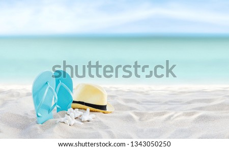 Beach summer holiday banner background. Flip flops and hat on sand near ocean. Summertime accessories on seaside. Tropical vacation and relax travel concept. Top view and copy space. Selective focus #1343050250