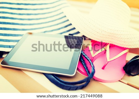 beach, summer, vacation, accessories and technology concept - close up of tablet pc computer and summer accessories on beach