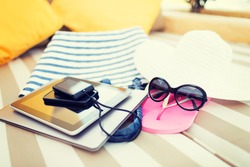 beach, summer vacation and technology concept - close up of tablet pc, notebook, smartphone and summer accessories on beach