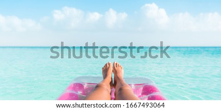 Beach summer vacation woman relaxing on pool float taking feet selfie pov of legs sunbathing relax on pink air mattress inflatable toy floating on blue ocean background panoramic banner.