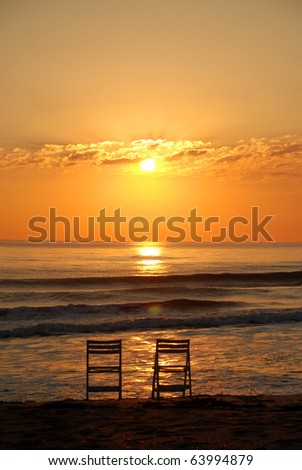 Beach Sun Rise with Two Lonely Chairs Space for Copy in Sky