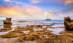 Beach sunset at Neil island Andaman India with naturals rocks and corals and sailing vessel at the horizon.