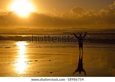 Beach sunset. Image of a man looking toward the sun with his hands raised. #58986754