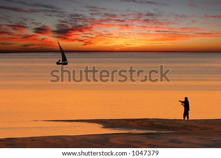 Beach sunset scene in Mozambique with fisherman and small sailboat (called a dhow) - stock photo