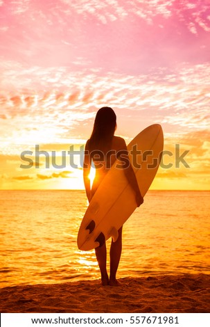 Stock Photo Beach sunset sexy surfer woman surfing lifestyle relaxing holding surfboard looking at ocean waves for surf. Active healthy living silhouette of sports athlete standing in colorful sky.